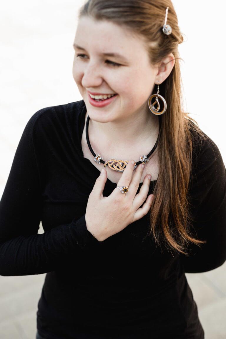smějící se dívka s prořezávaným náhrdelníkem a náušnicemi z kapslí