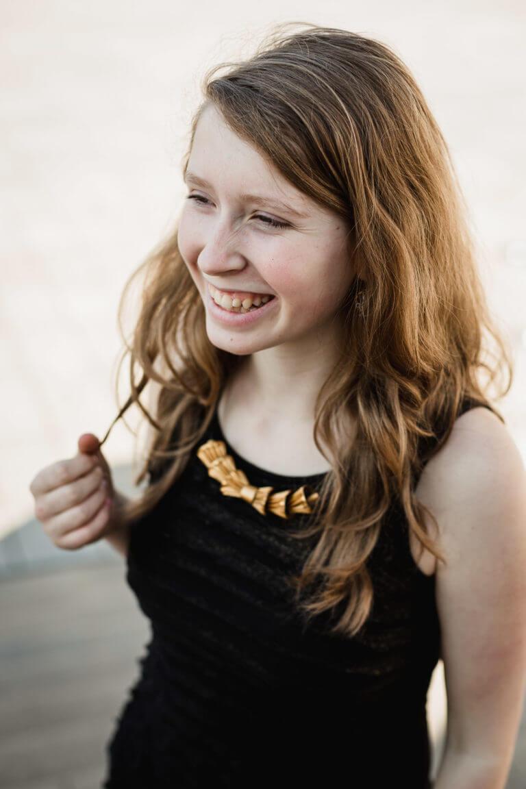 Rozesmátá dívka s elegantním upcyklovaným náhrdelníkem zlaté barvy